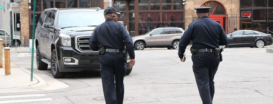Two police officers in uniform walking on the street.